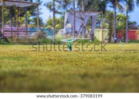 Garden sprinkler watering the green lawn - stock photo