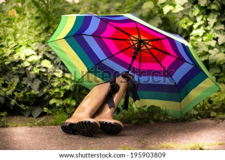 garden still life with water can, gum boots, and multicolored umbrella - stock photo