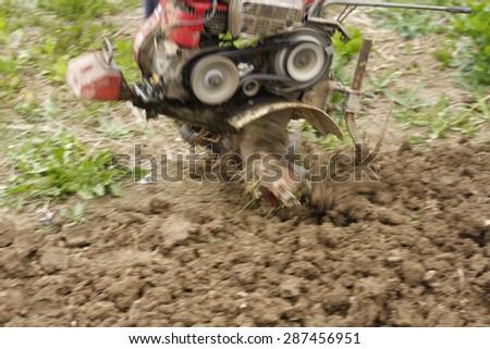 garden tiller working-motion blur - stock photo
