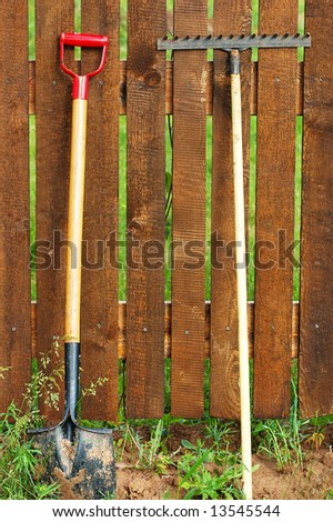 garden tool set over wood backyard fence - stock photo