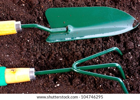 Garden tool with heap of organic compost background