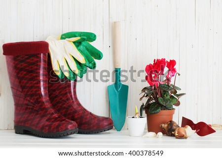 Garden tools and rubber boots on white wooden background