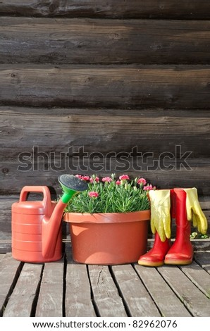 Garden tools (flower pot, watering can/ pot and rubber boots) vertical image - stock photo