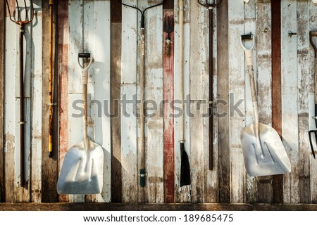 Garden tools hang on the wall - stock photo
