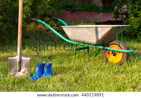 Garden tools on a green lawn. blue shovel and rubber boots.