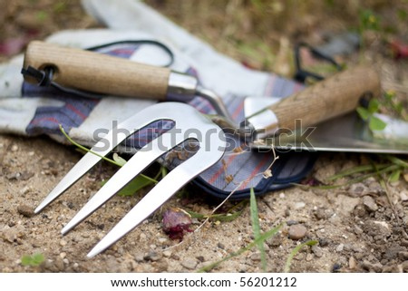 Garden tools: stainless steel trowel and rake and a pair of gloves. - stock photo