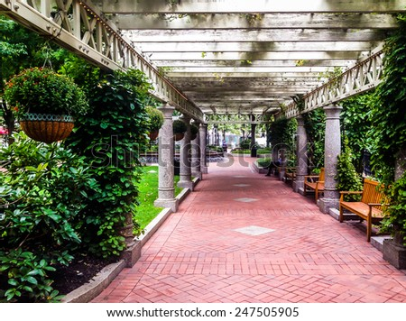 Garden trellis over a path and buildings at Norman B. Leventhal Park in Boston, Massachusetts. - stock photo
