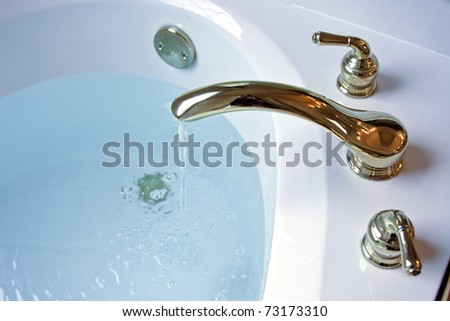 garden tub filling up with water from a gold plated faucet