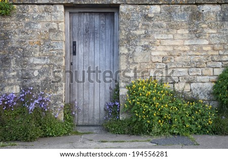 Garden wall with wooden door and flowers, Cotswolds, Chipping Campden, Gloucestershire, England. - stock photo