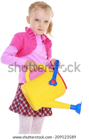 garden watering can in the hands of a charming girl.The concept of childhood and child development - stock photo