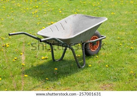 garden-wheelbarrow on green grass - stock photo
