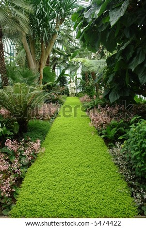 garden with a green path of grass to a statue - stock photo