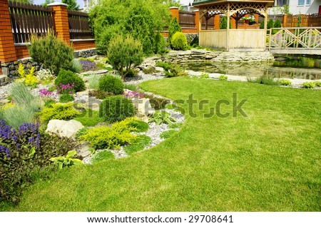 Garden with a lake and waterfall - stock photo