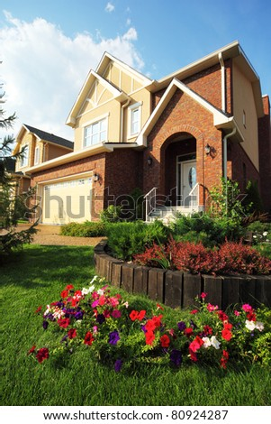 Garden with beautiful flowers in front of new two-storied brick cottage - stock photo