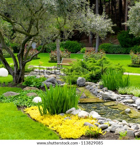 garden with pond and oliva trees in asian style - stock photo