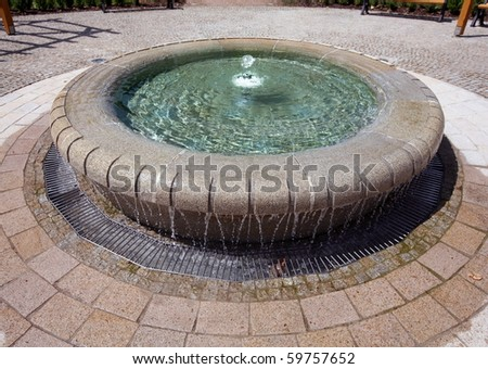 Garden with small fountain and benches around - stock photo