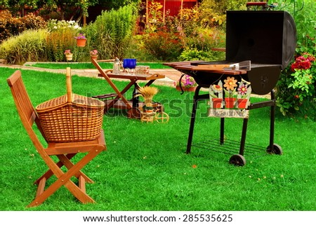 Garden Wooden Furniture, Picnic Hamper Basket, BBQ Grill, Sign Welcome, Wine Glasses On The Table, Plants, Trees and House In The Background. Backyard  BBQ Grill Party Or Picnic Concept - stock photo