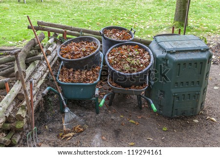 garden work during autumn season.  garden tools , wheelbarrow and buckets full with dry autumn leaves - stock photo