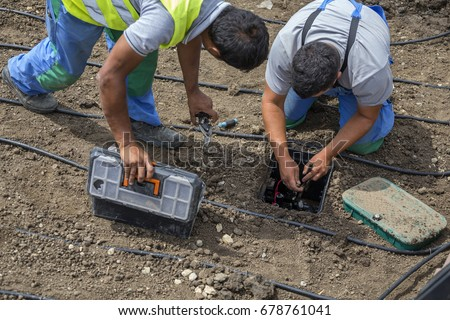 Garden workers installing irrigation control box for water plants with automatic watering system.