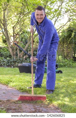 gardener at work, cleaning a garden path.with a red broom.