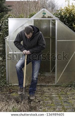 gardener at work, seasoan garden spring work,  gardener digging  over a vegetable garden. - stock photo