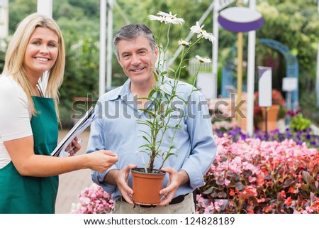 Gardener giving advice to customer while holding a flower and smiling - stock photo