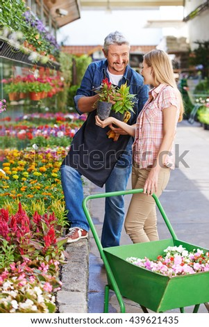 Gardener giving consultation to customer in front of a nursery shop
