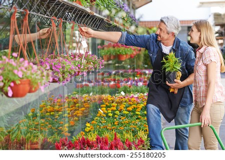 Gardener in front of nursery shop helping woman choosing the right flower - stock photo