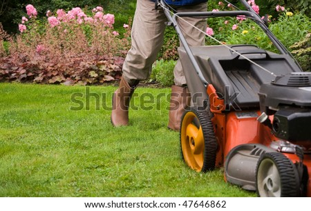 Gardener mowing the lawn. - stock photo