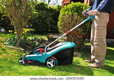 Gardener mowing the lawn in front of house using electric - stock photo