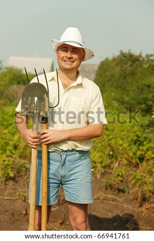 gardener posing  for the camera with his fork and shovel against summer time in garden - stock photo