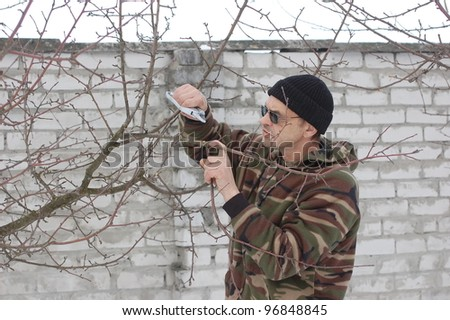 Gardener pruning the branches of apple tree in early spring. Near Kiev,Ukraine