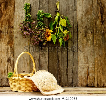Gardener's straw hat and basket of freshly cut oregano and herbs hanging on an aged barn board background. - stock photo