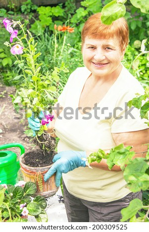 Gardener senior positive elderly woman is planting flowers in pot with dirt (soil) and roots. Caucasian active happy lady in her 60s in the summer garden. Mature female model involved in horticulture. - stock photo