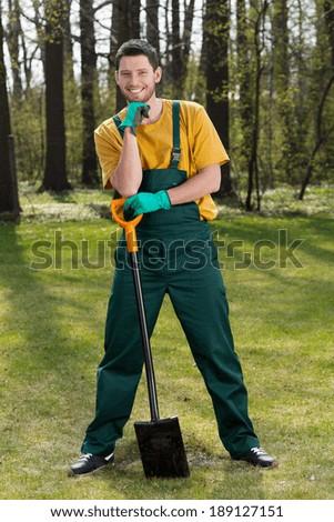 Gardener standing in garden with a spade - stock photo