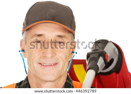 Gardener with trimmer and ear protectors - stock photo