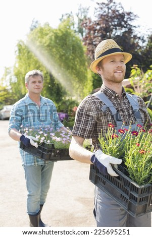 Gardeners carrying flower pots in crates at plant nursery - stock photo