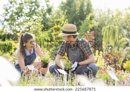 Gardeners talking while gardening at plant nursery - stock photo