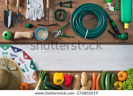 Gardening and farming tools on a wooden table and freshly harvested vegetables, blank copy space, top view - stock photo
