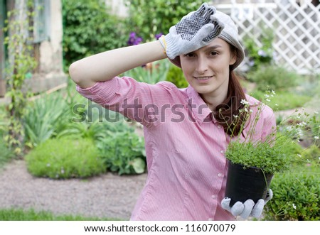 Gardening concept - tired woman with seedlings in the garden - stock photo