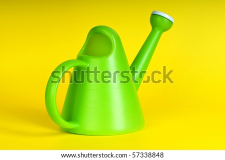 Gardening concept with green watering can on background