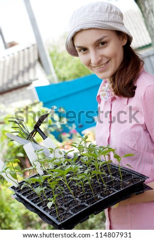 Gardening concept - woman with seedlings in the garden - stock photo