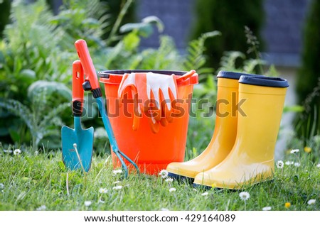 Gardening equipment and yellow rubber boots on grass with greenery in background - stock photo