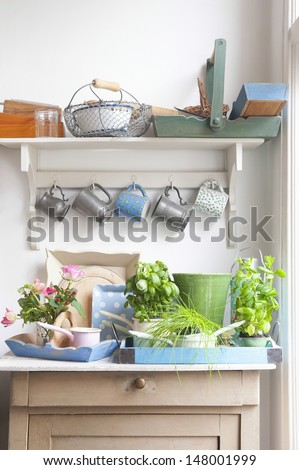 Gardening equipment on kitchen's dresser with cups hanging above it - stock photo