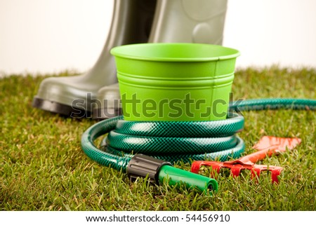 Gardening equipment placed on green grass with plants - stock photo