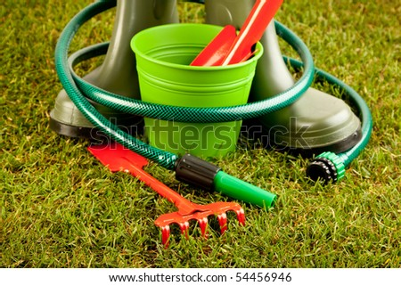 Gardening equipment placed on green grass with plants