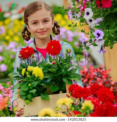 Gardening, flowers - Lovely girl with summer flowers in the garden center. - stock photo