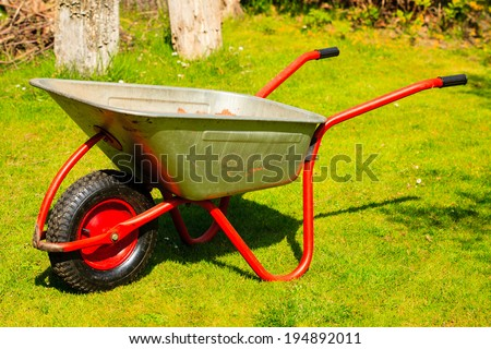Gardening. Garden metal wheelbarrow in the yard. Outdoor.