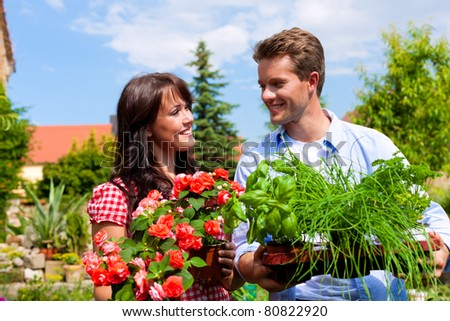 Gardening in summer - happy couple with fresh herbs and red flowers - stock photo