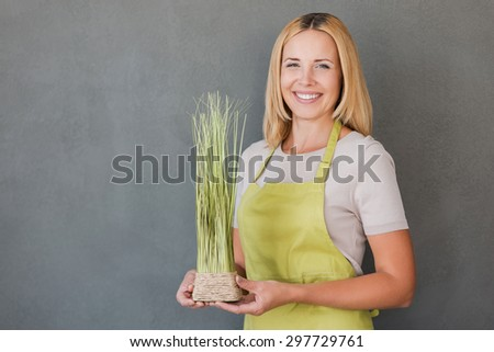 Gardening is my passion. Cheerful mature woman in green apron holding flower pot and smiling while standing against grey background  - stock photo